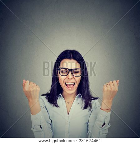 Happy Woman Exults Pumping Fists Celebrates Success On Gray Wall Background