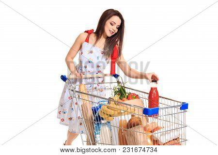 Smiling Young Woman Doing Grocery Shopping At The Supermarket, She Is Putting A Tomato Juice Bottle