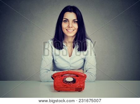 Happy Woman Sitting At Table With Vintage Red Telephone