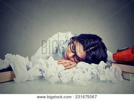 Young Woman Sleeping At Her Disorganized Desk