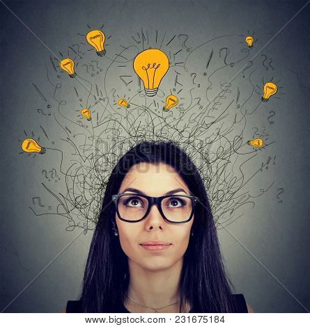 Serious Woman In Glasses With Many Ideas Light Bulbs Above Head Looking Up Isolated On Gray Wall Bac