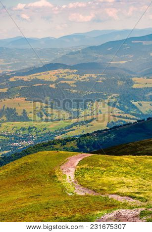 Road Down The Grassy Hill In To The Valley. Beautiful Mountainous Landscape. Wonderful Place For Wal