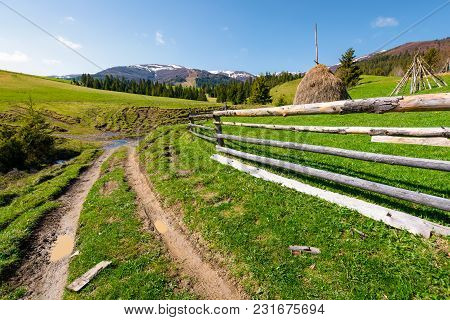 Beautiful Carpathian Countryside In Springtime. Dirt Road Down The Hill And Haystack Behind The Wood