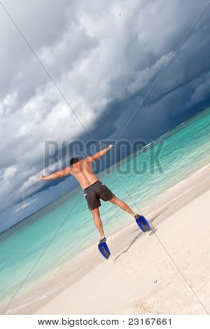 Tanned Man Jump In Blue Flippers On Sand Beach And Ocean