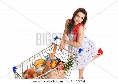 High Angle View Of Girl Smiling At Camera While Pushing A Shopping Cart Full With Groceries Isolated
