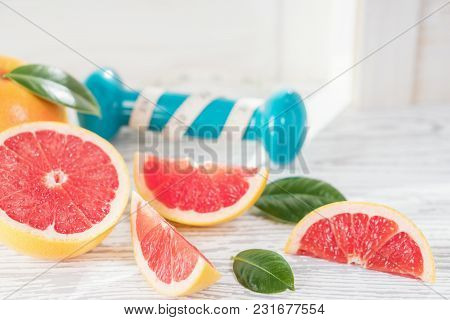 Fresh Red Grapefruit And Grapefruit Slices, Dumbbell And Measuring Tape, On Rustic White Wooden Tabl