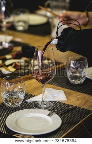 Served Table At Wine Tasting. Sommelier At Wine Tasting Pouring Red Wine From Decanter Into Glass