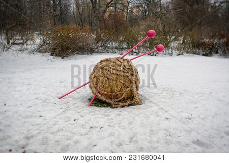 Ball Of Wool With Stuck Knitting Needles In The Snow In A Park. Composition Of Cold And Warm.