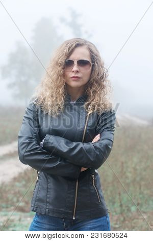 Beautiful Woman In A Leather Jacket And Glasses In The Fog