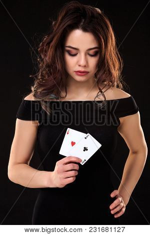 Young Woman Holding Playing Cards Against A Black Background. Gambling. Poker. Two Aces.