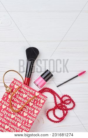 Feminine Beauty Background, Top View. Gift Bag, Nail Polish, Brush And Accessories On White Wooden B