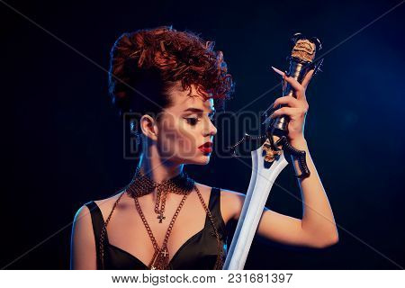Seductive And Fashionable Model With Bright Make Up Keeping Steel Sword With Black Skull. Woman Wear