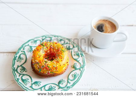 Yellow Donut And Coffee On Wood Background.