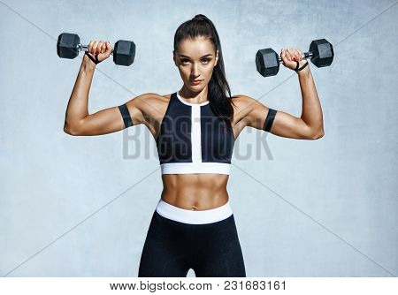Beautiful Young Woman Doing Exercises With Dumbbells. Photo Athletic Woman With Perfect Body On Grey