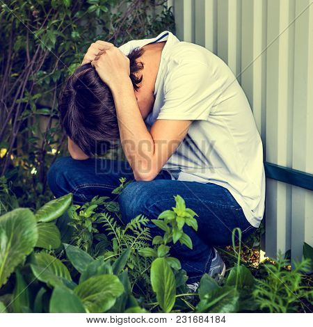 Toned Photo Of Sad Young Man Sit By The Wall Outdoor
