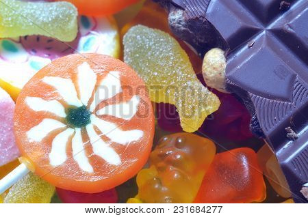 Macro Detail Of Lollipop, Gummy Bears, Chocolate And Sour Candy On Colored Smarties Background