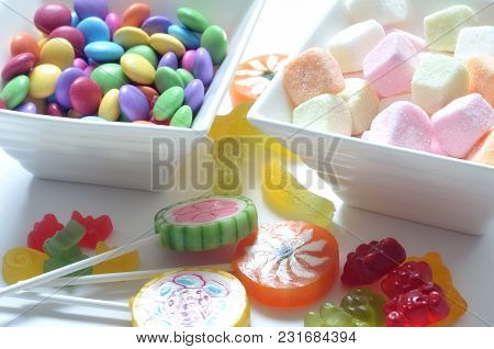 Two Ceramic Bowls Of Colored Smarties, Sour Candies, Lollipop And Gummy Bears On White Background