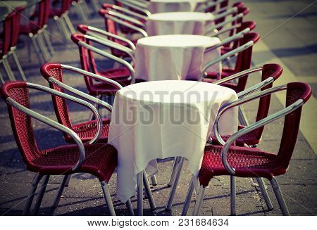Tables And Red Chairs In An Alfresco Cafe In The European City With Vintage Effect