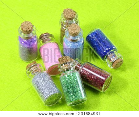 Some Glass Flasks With Glitter And A Green Background