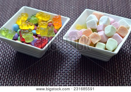 Two Ceramic Bowls Of Colored Smarties, Sour Candies And Gummy Bears On Bamboo Wooden Pad