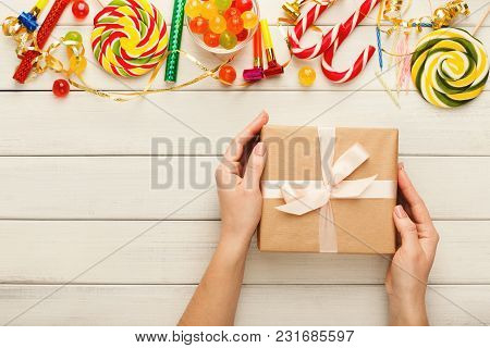 Female Hands With Present Box On White Wooden Background With Border Of Colorful Lollipops And Bon-b