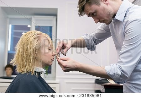 A Handsome Hairdresser Making Haircut For A Blonde Female Client In Hairdressing Salon. Selective Fo