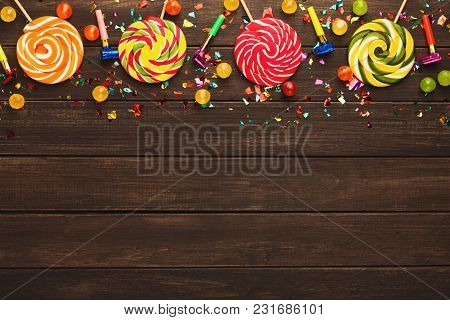 Border Of Colorful Spiral Lolipops, Confetti And Small Bon-bons On Rustic Wood. Birthday Party Decor