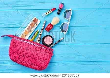 Female Cosmetics And Accessories Composition. Pink Cosmetics Bag With Makeup Products Spilling Out O