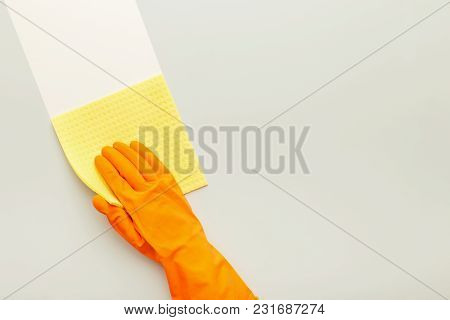 Hand In Protective Rubber Glove With Yellow Rag. Woman Washing White Surface With Micro Fiber Cloth,