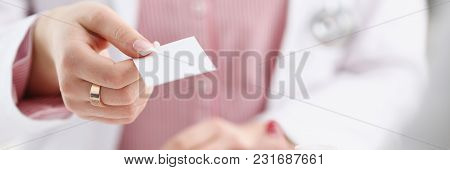 Female Physician Hand Give White Blank Calling Card To Businesswoman Closeup In Office. Physical Dis