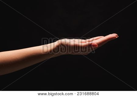 Holding Or Offering. Outstretched Female Hand, Girl Keeping Empty Palm On Black Isolated Background