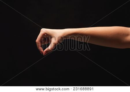 Caucasian Female Hand Picking Up Some Small Item On Black Isolated Background, Cutout, Copy Space