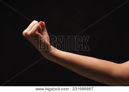 Female Hand Clenched Fist On Black Isolated Background, Low Key, Cutout