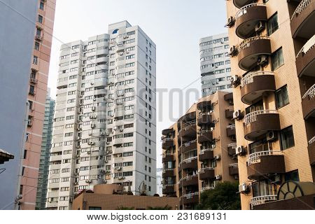 High-rise Buildings In Shanghai With Balconies And Air Conditioning Against The Blue Sky.