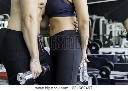 Beautiful Young Sporty Sexy Athletic Couple  Showing Muscle And Workout In Gym During Photo Shooting