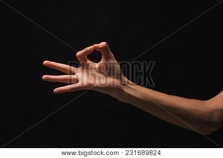 Caucasian Male Hand Picking Up Some Small Item On Black Isolated Background, Cutout, Copy Space