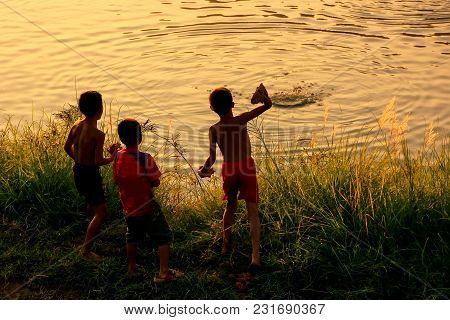 Local Kids Throuwing Rocks In Nam Song River At Sunset, Vang Vieng, Laos. Vang Vieng Is A Popular De