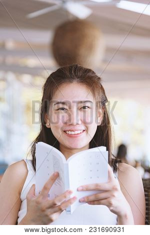 Beautiful Asian Woman Has Smile And Hides His Face Behind A Book With Relaxing Time On The Holiday A