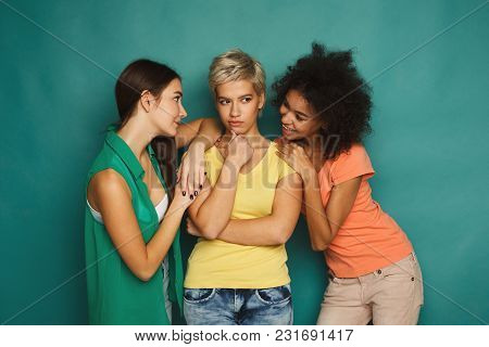 Tricky Female Friends Having Fun At Blue Background. Three Young Women Having Plan, Gossiping And La