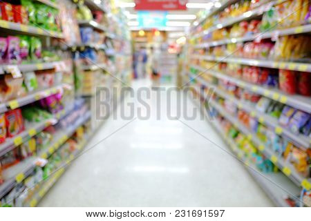 Blurred A Supermarket With A Product Packaging On A Shelf And A Customer Walking Around