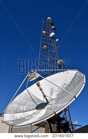A Television Satellite Dishes For Transmitting Signal And A Tall Signal Tower.