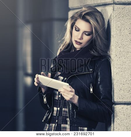 Young fashion woman using digital tablet computer in city street Stylish female model wearing black leather jacket and blue jeans