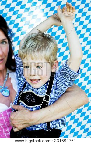 Portrait Of Bavarian Boy With Mother On Blue And White Background