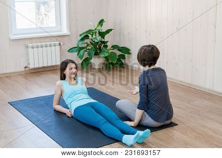 Young Woman Lying On Mat In Class And Talking To Trainer Of Body-oriented Psychotherapy.