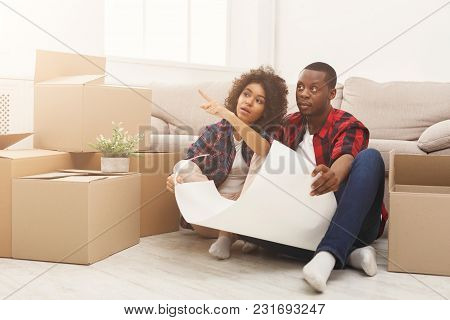 Happy African-american Couple Unpacking Moving Boxes And Discussing Interior Design In New Apartment