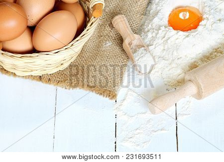 Wicker Basket Of Eggs, Heap Of Flour With Yolk, Rolling Pin And Canvas Bag On White Wooden Desk - Ba