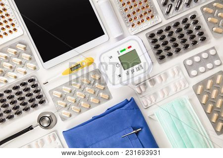 Directly Above Shot Of Various Pills In Blister Packs By Blood Pressure Machine With Tablet Computer