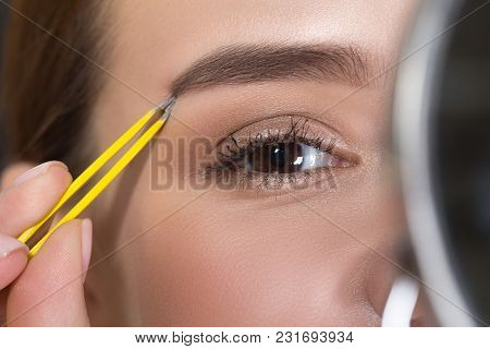 Always Perfect. Close Up Part Of Face Of Positive Young Woman Is Plucking Eyebrows While Using Tweez
