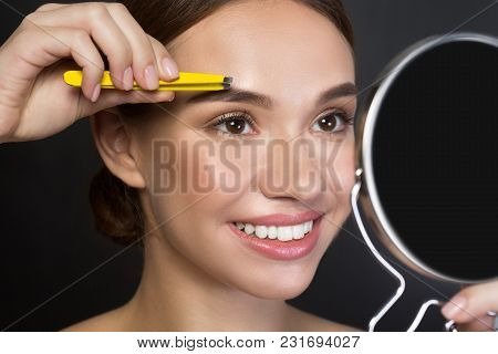 Close Up Portrait Of Gorgeous Young Woman Is Standing And Using Tweezers While Looking At The Mirror