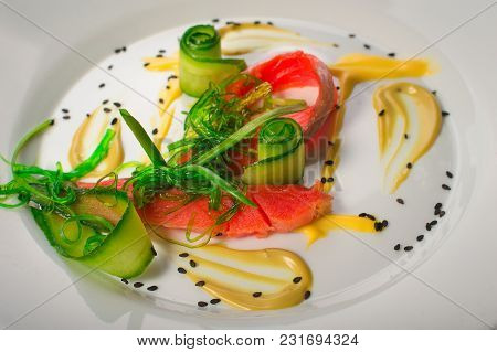 Dish With Salmon, Seaweed And Cucumber. Old Black Rustic Background. Top View.